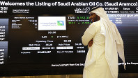 A Saudi stock market official smiles as he watches the stock market screen displaying Saudi Arabia's state-owned oil company Aramco after the debut of Aramco's initial public offering (IPO) on the Riyadh's stock market in Riyadh, Saudi Arabia, on Dec. 11, 2019. (AP Photo/Amr Nabil)