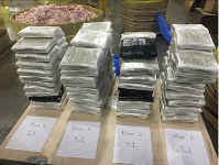 In this December 2019 photo provided by the Cleveland County Sheriff's Office in Shelby, N.C., approximately $3 million in cash, wrapped in plastic, is displayed near the barrels of raw pork shoulder in which it was discovered in. (Cleveland County Sheriff's Office via AP)