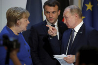 German Chancellor Angela Merkel, left, listens to French President Emmanuel Macron, center, and Russian President Vladimir Putin during a joint press conference with Ukrainian President Volodymyr Zelenskiy, at the Elysee Palace in Paris, on Dec. 9, 2019. (Charles Platiau/Pool via AP)