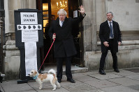 Britain's Prime Minister and Conservative Party leader Boris Johnson is seen with his dog Dilyn as he leaves after voting in the general election at Methodist Central Hall, Westminster, London, on Dec. 12, 2019. (AP Photo/Frank Augstein)