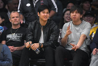 Los Angeles Angels pitcher Shohei Ohtani, center, watches along with Flea, left, of the Red Hot Chili Peppers, and Ohtani's interpreter Ippei Mizuhara during the second half of an NBA basketball game between the Los Angeles Lakers and the Washington Wizards, on Nov. 29, 2019, in Los Angeles. (AP Photo/Mark J. Terrill)