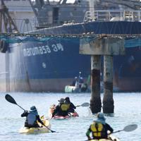 埋め立てる土砂を運ぶ運搬船の積み込みに、カヌーに乗って抗議する人たち=沖縄県名護市で2019年12月13日午後0時58分、津村豊和撮影