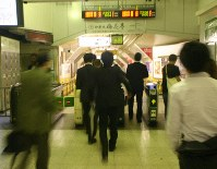 This file photo shows commuters rushing to a train platform at midnight. (Mainichi)