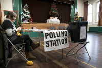 Chris Johnson, 62, does her knitting while awaiting people to vote at the polling station in Nenthead Village Hall in Cumbria, England Thursday Dec. 12, 2019. (Owen Humphreys/PA via AP)