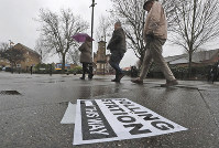 A polling station signpost lies on the pavement as voters approach a polling station in Twickenham, England, on Dec. 12, 2019. (AP Photo/Frank Augstein)
