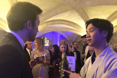 品評会で参加者に「だいやめ」を勧める浜田酒造の浜田光太郎さん(右)=ロンドンで