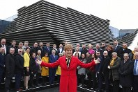 Scottish First Minister Nicola Sturgeon poses with newly elected MPs of Scottish National Party (SNP) during a photo opportunity as they gather outside the V&A Museum in Dundee, Scotland, Saturday Dec. 14, 2019. (Andrew Milligan/PA via AP)