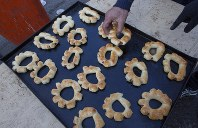 In this photo taken Monday, Dec. 9, 2019, a volunteer chef serves free portions of the popular sweets of Cherek, baked wheat flour bread stuffed with dates, to protester in the center of Baghdad, Iraq. (AP Photo/Nasser Nasser)