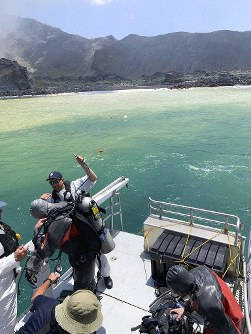Police divers prepare to search the waters near White Island off the coast of Whakatane, New Zealand, Saturday Dec.14, 2019. (New Zealand Police via AP)
