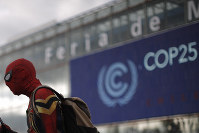 A man dressed in a Spiderman costume walks outside of the COP25 climate talks congress in Madrid, Spain, on Dec. 14, 2019. (AP Photo/Manu Fernandez)