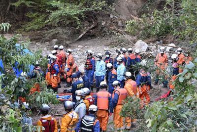 台風19号で土砂災害が発生した廻倉地区で、行方不明者を捜索するため集まった警察官ら=宮城県丸森町で
