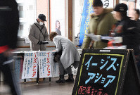 A passerby signs a document opposing the deployment of an Aegis Ashore land-based missile defense system to the Ground Self-Defense Force's Araya Maneuver Area, at a concourse in JR Akita Station on Dec. 15, 2019. (Mainichi/Shun Kawaguchi)