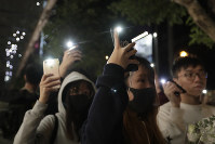 Attendees hold up their lit mobile phones to mark the six months anniversary memorial for a man who fell to his death while hanging a protest banner against an extradition bill, in Hong Kong on Dec. 15, 2019 in Hong Kong. (AP Photo/Mark Schiefelbein)