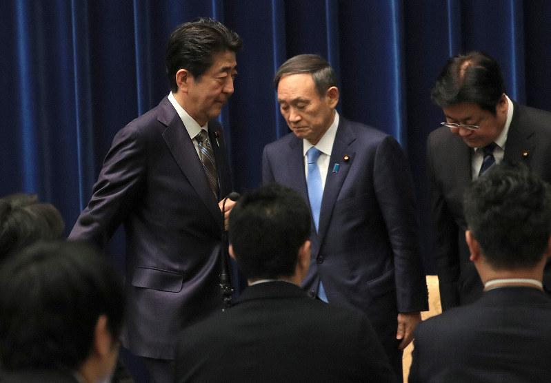 臨時国会閉会後、記者会見を終えて退出する安倍晋三首相(左)。会見の冒頭であえて「桜」の問題に触れなかった=12月9日