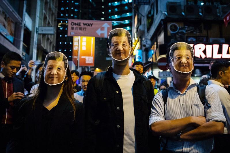 習近平の仮面をかぶりデモに参加した香港市民(Bloomberg)