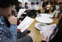 NO YOUTH NO JAPANの呼びかけで集まったイベントで資料の新聞記事を読む参加者たち=東京都千代田区で2019年12月18日、宮武祐希撮影