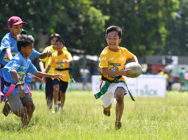 裸足でピッチを走る子どもたち=フィリピン・ネグロスオクシデンタル州タリサイ市で2017年8月5日、川平愛撮影