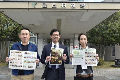 長野県豊丘村のふるさと納税のパンフレットを手に返礼品をPRする長谷川雅さん(中央)ら村総務課の3人。地道な取り組みが村の固定ファンを増やした=同村役場で
