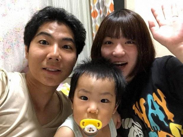 東京都内の自宅で写真に収まる夫の亮さん(左)と息子の健くん(中央)、妻の茜さん=2019年8月