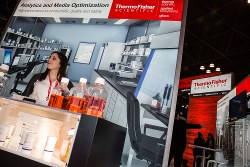An employee stands behind the Thermo Fisher Scientific Inc. booth during the International Pharmaceutical Expo (Interphex) in New York, U.S., on Tuesday, March 21, 2017. Interphex is a pharmaceutical, biotechnology, and medical device development and manufacturing event offering access to new business trends and strategies. Photographer: Timothy Fadek/Bloomberg