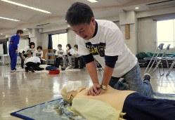 心臓マッサージの実習をする男性