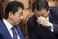 麻生太郎財務相(右)の「安倍4選支持」発言は、首相の求心力を保つのが狙いか(Bloomberg)