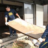被災した住宅から畳など家財道具を運び出すラグビー部員たち=栃木県栃木市内で