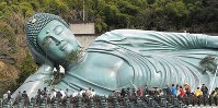 Worshippers use bamboo branches to dust a giant Buddha during an annual year-end cleaning event at Nanzoin Temple in the town of Sasaguri, Fukuoka Prefecture, in southwestern Japan, on Dec. 26, 2019. (Mainichi/Toyokazu Tsumura)