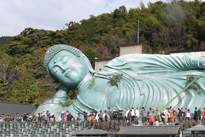 竹ザサでほこりが払われる釈迦涅槃像=福岡県篠栗町で2019年12月26日午前11時13分、津村豊和撮影