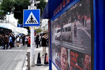 中国に広がる交通違反者暴露台。電動バイクで信号無視をした女性の顔と個人情報がさらされていた=中国江蘇省無錫で11月