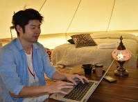 A person on a vacation with his family works remotely from a campsite in the town of Kushimoto, Wakayama Prefecture, on Aug. 23, 2019. (Mainichi/Akane Imamura)