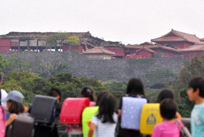 焼け落ちた首里城(奥)を見つめる、下校途中の小学生たち=那覇市で10月31日午後4時7分、森園道子撮影