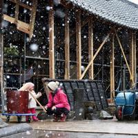 餅つき大会の前日、届けられた「福幸之臼」で餅をつく練習をする北原彩結ちゃん(左)と母祥子さん。初めて餅つきする彩結ちゃんは自分の背丈ほどのきねを持ち、祥子さんと「ぺったん、ぺったん」と声をそろえていた=長野市の妙笑寺で2019年12月27日、滝川大貴撮影