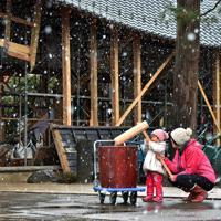 餅つき大会の前日、届けられた「福幸之臼」で餅をつく練習をする北原彩結ちゃん(2)と母祥子さん(39)。彩結ちゃんにとっては初めての餅つき。「ぺったん、ぺったん」と言いながら祥子さんが持つきねに手を添えていた=長野市の妙笑寺で2019年12月27日、滝川大貴撮影