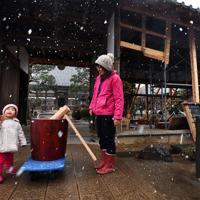 餅つき大会の前日、届けられた「福幸之臼」で餅をつく練習をする北原彩結ちゃん(2)と母祥子さん(39)。彩結ちゃんにとっては初めての餅つき。祥子さんのかけ声に合わせて「ぺったん、ぺったん」と声をそろえていた=長野市の妙笑寺で2019年12月27日、滝川大貴撮影