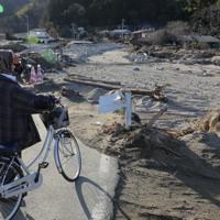 川が氾濫して流木などが流れ、田畑や建物が土砂に埋まったままの場所を見て回る女性。「ここに自分の畑や田んぼがあったんだけど、来年は野菜つくれるんだろうか」と話した=宮城県丸森町で2019年12月25日、和田大典撮影
