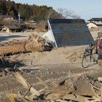 川が氾濫して流木などが流れ、田畑や建物が土砂に埋まったままの道を歩く女性。「ここに自分の畑や田んぼがあったんだけど、来年は野菜つくれるんだろうか」と話した=宮城県丸森町で2019年12月25日、和田大典撮影