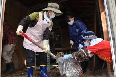 台風で発生した災害ごみの片付けを手伝うボランティアの人々=宮城県丸森町金山地区で