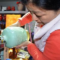 30年ものの黄酒の老酒を大切そうに注ぐ車頼さん=中国浙江省紹興で2019年11月9日、浦松丈二撮影