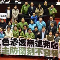 「民主主義を守る措置は一刻の猶予も許さない」などと記した横断幕を掲げ「反浸透法案」の必要性を訴える民進党の立法委員(国会議員)ら=台湾立法院で12月31日