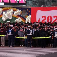 年明けを前に、大勢の人が集まったスクランブル交差点の警備に当たる警察官ら=東京都渋谷区で2019年12月31日午後9時5分、北山夏帆撮影