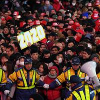 渋谷駅前に集まり、押し合いとなった大勢の人を押さえる警備員ら=東京都渋谷区で2019年12月31日午後11時53分、北山夏帆撮影