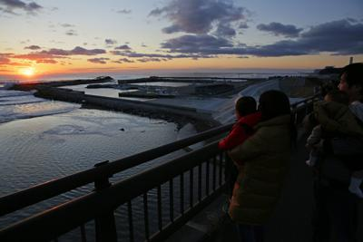 富岡漁港で2020年の初日の出を見つめる家族連れ。同漁港は東日本大震災後使えなくなっていたが、昨年7月に復旧して再開した。富岡町では東京電力福島第1原発事故による避難指示が続いている帰還困難区域のうち、JR常磐線夜ノ森駅周辺で3月10日に避難指示が解除される予定。朝日を背に家族で記念撮影をした藤田秀明さん(48)は「今年は家族みんなが元気で過ごせるといい。夜ノ森駅再開などでちょっとでも町に人が集まってくれれば」と話した=福島県富岡町で2020年1月1日午前6時51分、和田大典撮影