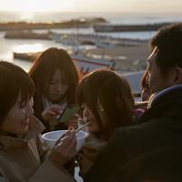 2020年の初日の出を望む富岡漁港で町民がふるまった豚汁を食べる家族連れ。同漁港は東日本大震災後使えなくなっていたが、昨年7月に復旧して再開した。富岡町では東京電力福島第1原発事故による避難指示が続いている帰還困難区域のうち、JR常磐線夜ノ森駅周辺で3月10日に避難指示が解除される予定=福島県富岡町で2020年1月1日午前7時12分、和田大典撮影