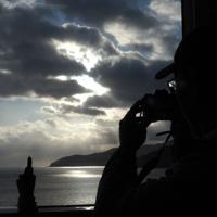 「三鉄初日の出号」から雲の間に見える朝日を撮影する乗客=岩手県大船渡市で2020年1月1日午前8時16分、米田堅持撮影