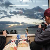 「三鉄初日の出号」の車内で初日の出を撮ろうとカメラやスマホを構える乗客=岩手県大船渡市で2020年1月1日午前6時53分、米田堅持撮影