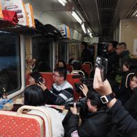 「三鉄初日の出号」の車内から初日の出を見ようとカメラやスマホを持って待つ乗客たち=岩手県大船渡市で2020年1月1日午前6時51分、米田堅持撮影