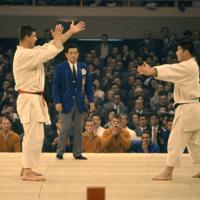 柔道無差別級決勝で、神永昭夫選手(右)と対戦するオランダのアントン・ヘーシンク選手。神永選手は敗れ、銀メダル