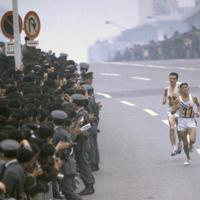 マラソンで多くの観客が詰めかける中、約38キロ地点の新宿駅南口を2位で通過する円谷幸吉選手は銅メダルを獲得した。左はハンガリーのヨゼフ・シュト選手