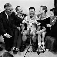 重量挙げフェザー級表彰式後、記者に囲まれる金メダルの三宅義信選手(中央)。(左から)三宅選手の父・栄三郎さん、銅メダルでポーランドのミェチスワフ・ノバック選手。三宅選手、銀メダルで米国のアイザック・バーガー選手、三宅選手の母・タケさん=中村太郎撮影